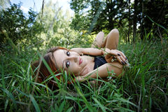 Pretty redhead girl lying on the grass Stock Photo