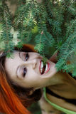 Pretty redhead girl near the tree Royalty Free Stock Images