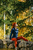 Pretty redhead girl sitting on stone in park Stock Photography