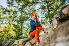 Pretty redhead girl sitting on stone in park Stock Photos