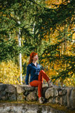 Pretty redhead girl sitting on stone in park Royalty Free Stock Images