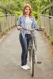 Pretty redhead with her bike smiling at camera Royalty Free Stock Photography