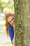 Pretty redhead hiding behind a tree. On college campus Royalty Free Stock Image