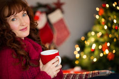Pretty redhead holding mug of hot drink Stock Photography