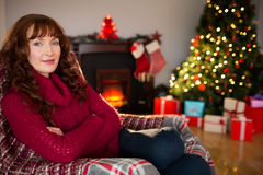 Pretty redhead in jumper sitting on the armchair at christmas Stock Photos