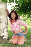 Pretty redhead leans on a tree Stock Photo