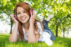 Pretty redhead listening to music in the park Royalty Free Stock Photography