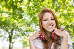 Pretty redhead listening to music in the park Royalty Free Stock Image