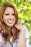 Pretty redhead listening to music in the park Royalty Free Stock Images