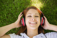 Pretty redhead lying on grass listening to music Royalty Free Stock Photos