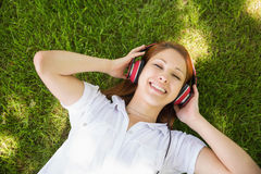 Pretty redhead lying on grass listening to music Stock Images