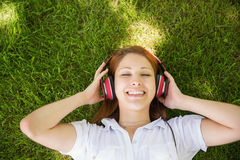 Pretty redhead lying on grass listening to music Stock Image