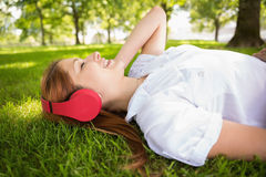 Pretty redhead lying on grass listening to music Royalty Free Stock Photography