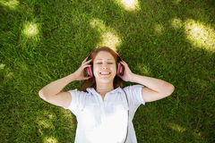 Pretty redhead lying on grass listening to music Royalty Free Stock Photo