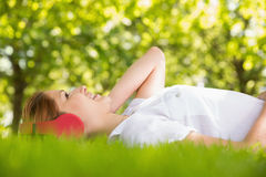 Pretty redhead lying on grass listening to music Royalty Free Stock Image