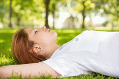 Pretty redhead lying on grass relaxing Royalty Free Stock Image