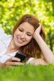 Pretty redhead lying on the grass sending a text Royalty Free Stock Photo
