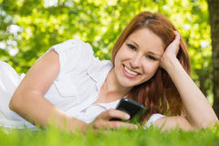 Pretty redhead lying on the grass sending a text Stock Photos