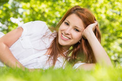 Pretty redhead lying on the grass smiling at camera Royalty Free Stock Images