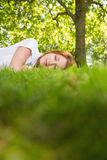 Pretty redhead lying on the grass Stock Images