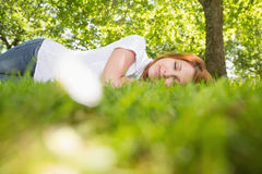 Pretty redhead lying on the grass Stock Photos
