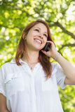 Pretty redhead on the phone in the park Stock Photos