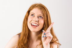 Pretty redhead pointing and looking up Stock Image
