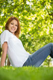 Pretty redhead relaxing in the park smiling at camera Stock Images