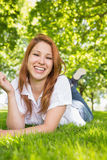 Pretty redhead relaxing in the park Stock Images