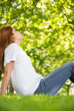 Pretty redhead relaxing in the park Royalty Free Stock Photo