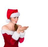 Pretty redhead in santa outfit blowing over hands Royalty Free Stock Photography