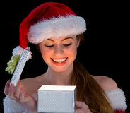 Pretty redhead in santa outfit opening a gift Royalty Free Stock Image