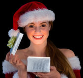 Pretty redhead in santa outfit opening a gift smiling at camera Stock Images