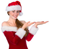 Pretty redhead in santa outfit presenting with hands Royalty Free Stock Photo