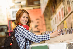 Pretty redhead searching a vinyl and smiling at camera Stock Photos