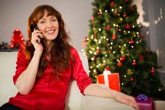 Pretty redhead sitting on the couch phoning Royalty Free Stock Photos