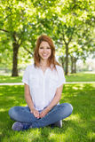 Pretty redhead smiling at camera in the park Royalty Free Stock Images