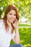 Pretty redhead smiling at camera in the park Stock Images