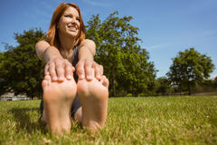Pretty redhead smiling stretching in park. On a sunny day stock photos