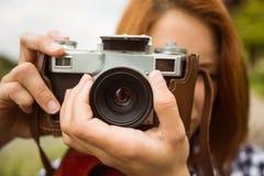 Pretty redhead taking a picture with retro camera Stock Photos