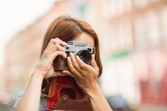 Pretty redhead taking a picture with retro camera Stock Photo