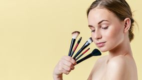 Pretty redhead teenage girl with freckles, looking down, holding diverse make up brushes. Model with light nude make-up. stock images
