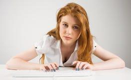 Pretty redhead typing on keyboard Stock Photo