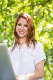 Pretty redhead using her laptop in the park Royalty Free Stock Photography