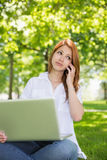 Pretty redhead using her laptop while phoning in the park Royalty Free Stock Photo