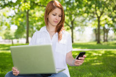 Pretty redhead using her laptop while texting in the park Stock Photo