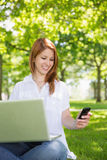 Pretty redhead using her laptop while texting in the park Royalty Free Stock Images