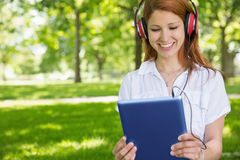 Pretty redhead using her tablet pc while listening to music in the park Stock Photos