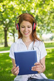 Pretty redhead using her tablet pc while listening to music in the park Royalty Free Stock Images