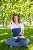 Pretty redhead using her tablet pc while listening to music in the park Stock Image